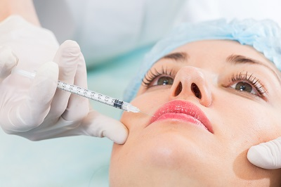 Woman receiving a botox injection in her lips